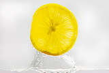 Lemon slice jumping out of water in white background