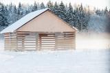wooden large barn in a snowy field near the forest. winter foggy landscape. corral in a winter field - 241398121