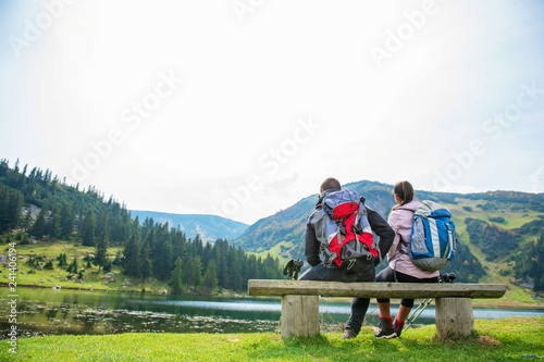 Leinwanddruck Bild young couple of backpackers near the lake in mountains