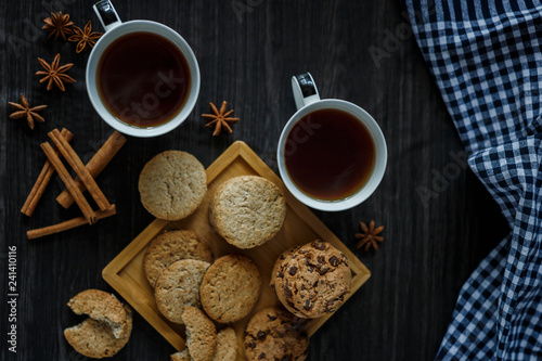 Two cups of tea and various cookies on dark wooden background
