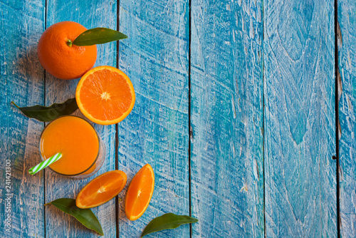 Orange juice and fresh oranges on wooden table