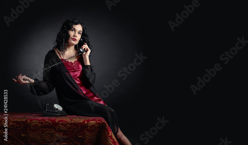 Portrait of attractive brunette  in negligee with old phone. - 241428533