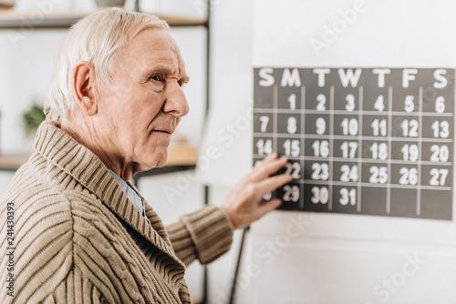 Foto Murales selective focus of senior man touching wall calendar and remembering dates