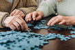 cropped view of retired couple playing with puzzles at home - 241431796