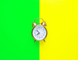 Leinwanddruck Bild - Alarm clock showing eight o'clock on bright duo tone yellow neon green background. Flat lay. Morning sunlight. New day beginning waking up energy planning self-organization concept