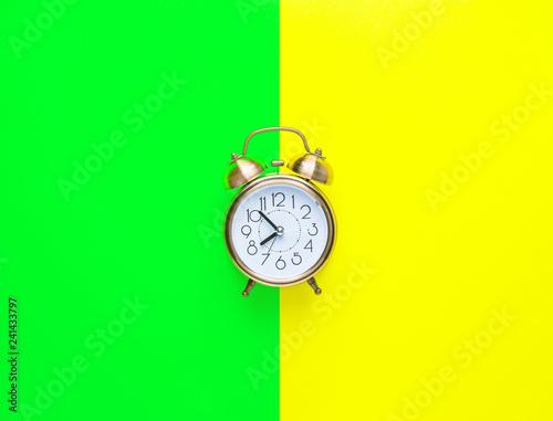 Leinwanddruck Bild Alarm clock showing eight o'clock on bright duo tone yellow neon green background. Flat lay. Morning sunlight. New day beginning waking up energy planning self-organization concept