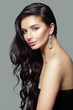 Leinwanddruck Bild - Attractive woman with long curly hair, makeup and diamond jewelry earrings