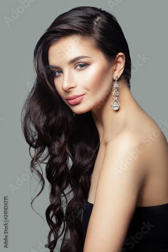 Leinwanddruck Bild Attractive woman with long curly hair, makeup and diamond jewelry earrings