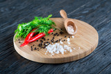 rock salt lies on a wooden surface against the background of grains of black pepper, red pepper and dill - 241439906