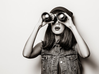 Portrait of young style hipster girl with binoculars . Image in black and white color style