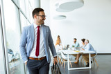 Young businessman leaves a meeting while other people stay in office - 241450749