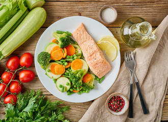 Steam salmon and vegetables, Paleo, keto, fodmap diet. White plate on old rustic wooden table, top view.