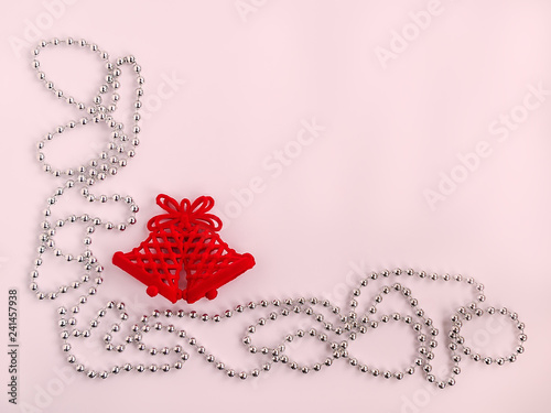 Two red Christmas bells and silver colored bead christmas garland on a pink pastel background, festive flat lay, top view, copy space