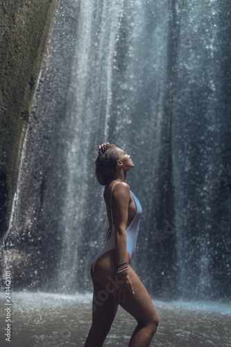 Beautiful girl in a blue swimsuit enjoys a magnificent tropical waterfall  - 241462301