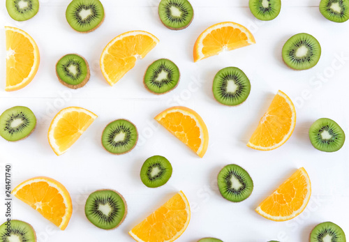Pattern with oranges and kiwi slices on a white wooden background. The basis for the booklet, the background for the banner. Basis for design with tropical fruits