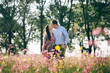 Leinwanddruck Bild - Beautiful young couple holding hands and walking in sunshine in spring meadow with pink flowers. Happy family smiling in green field in sunlight. Romantic moments. Valentine day.