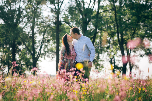 Leinwandbild Motiv Beautiful young couple holding hands and walking in sunshine in spring meadow with pink flowers. Happy family smiling in green field in sunlight. Romantic moments. Valentine day.