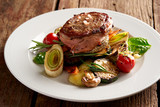 Leg of lamb steak wrapped in bacon with grilled vegetables - 241483905
