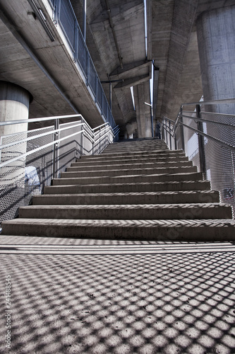 Foto Murales light and shadows on stairs under urban city  bridge background