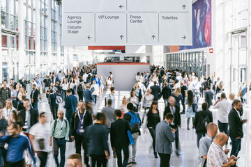 blurred people walking in a modern hall of a trade fair