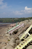 3096 Deck chairs strewn about stones on beach in Goa