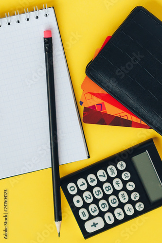 Flat lay composition with notepad, pencil, wallet with different credit cards and calculator on yellow bright background - 241504123