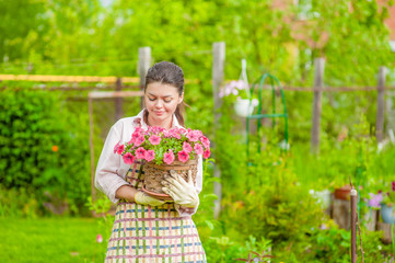 Young woman with flowers at back yard. Empty space for text