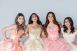 Four Hispanic Girls In Quinceanera Dresses