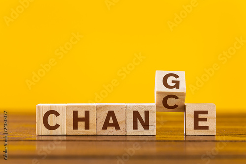 Change concept. Wooden letters on a yellow background
