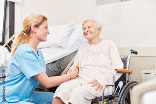 Altenpflegerin betreut Senior Frau im Rollstuhl - 241520163
