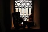 Contrazluz de una vieja ventana con rejas y motivos islámicos en Marrakech, Marruecos.