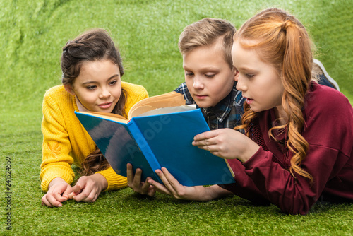 cute preteen schoolkids lying on green lawn and reading book