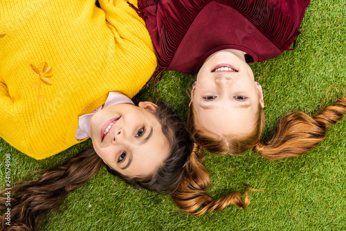 top view of smiling schoolgirls lying head to head on lawn