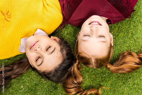 top view of cute schoolgirls with closed eyes lying head to head on lawn