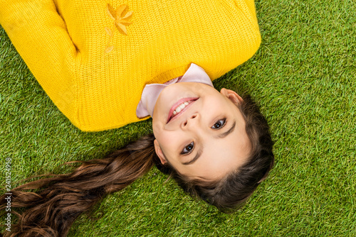top view of cute schoolgirl in yellow sweater with long hair lying on lawn and looking at camera