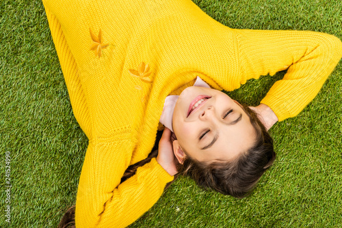 top view of cute schoolgirl in yellow sweater lying on lawn with closed eyes
