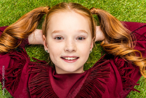 close up view of cute schoolgirl lying on lawn and looking at camera