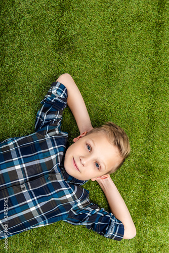 top view of cute boy lying on lawn and looking at camera