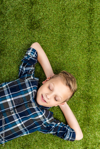 top view of cute boy lying on lawn with closed eyes