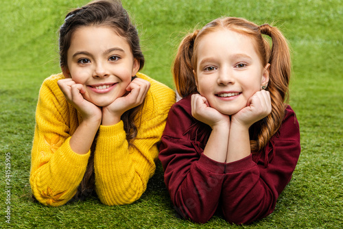 smiling schoolgirls lying on lawn and looking at camera
