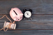 alarm clock piggy bank on old wood background - 241530143