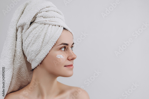 Woman with a towel on her head looking above with face moisturizer near eyes. Causing moisturizer cream onto her face. Skin care and beauty concept. Place for text