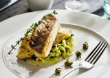 Fillet of halibut on a pillow of stewed leeks on the white plate. - 241542316