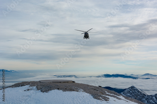 Mountain rescue helicopter landing to pick up wounded.