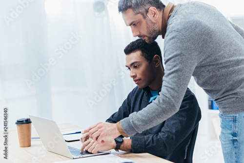 bearded mentor helping young colleague working with laptop in office