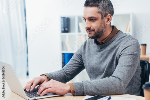 Poster handsome smiling bearded businessman working with laptop in office