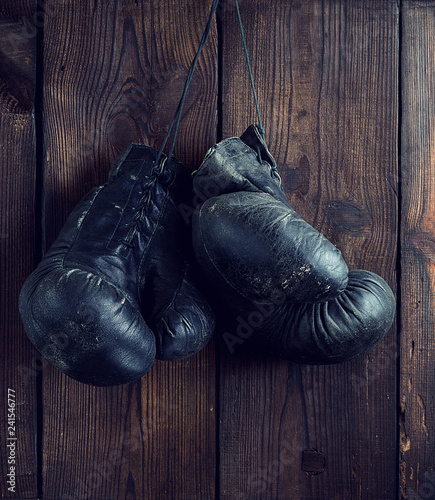 old shabby black leather boxing gloves hanging on a nail