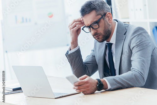 concentrated businessman in eyeglasses using smartphone and working with laptop in office