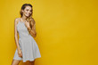 Fashionable and sexy blonde model girl with the attractive smile and with gentle makeup, in white striped dress adjusting her hairstyle and posing at the yellow background, isolated