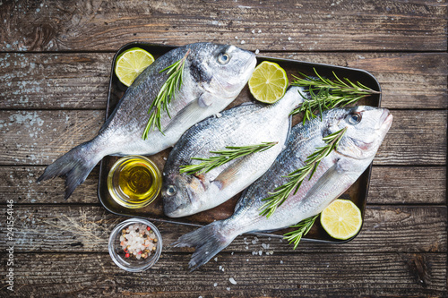 Fresh raw Dorado or sea bream with spices, herbs, lemon and salt over wooden background Top view - 241554146